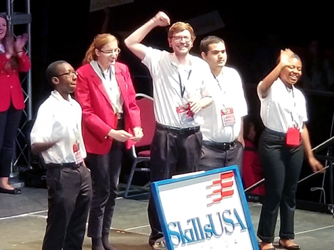 Group of diverse PHSC Skills USA competitors celebrating on stage.