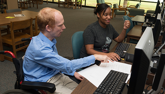 man in wheelchair tutoring a female student.