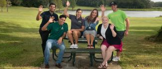 Diverse group of male and female students at picnic bench waving to camera