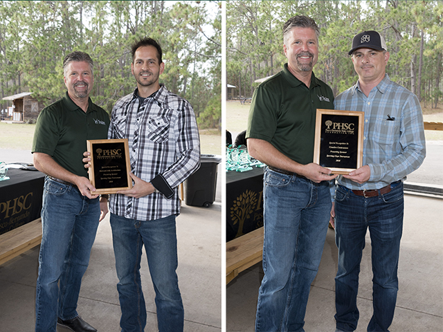 Man presenting plaques to two different men outdoors.